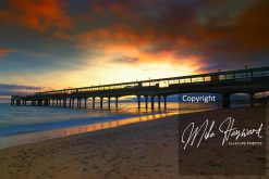 The sun peeks through the clouds as it sinks behind the pier