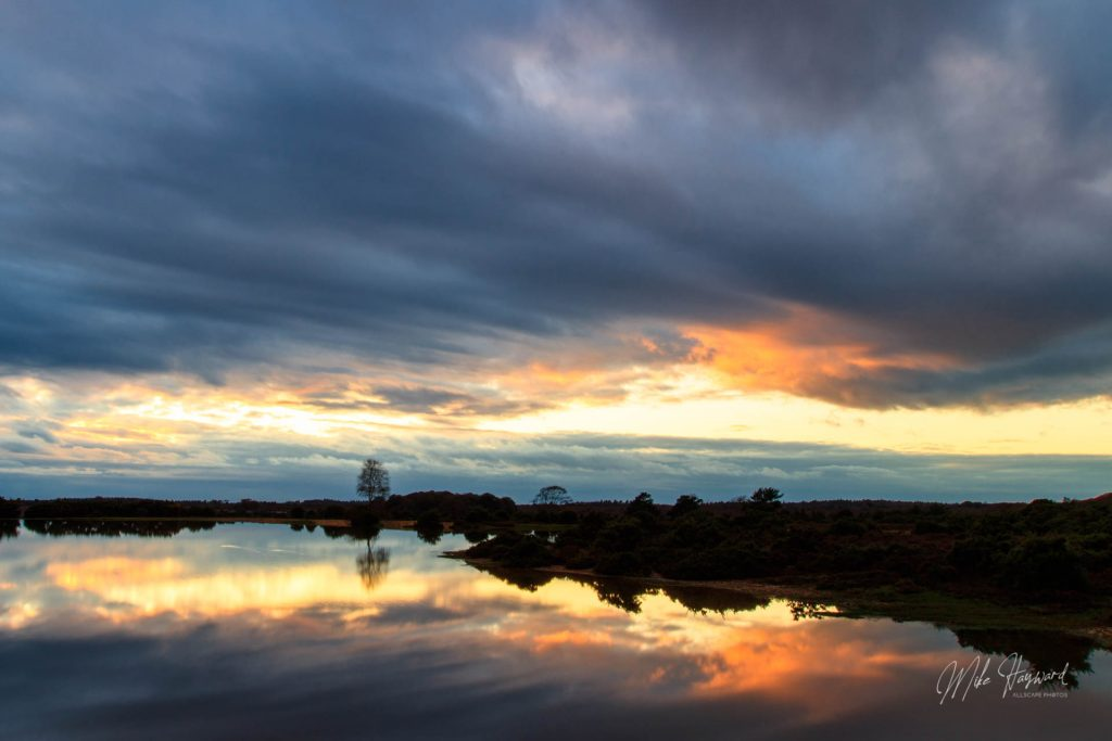 Cloud covers the sunset and produces darks and oranges reflected in the calm water surface of the pond
